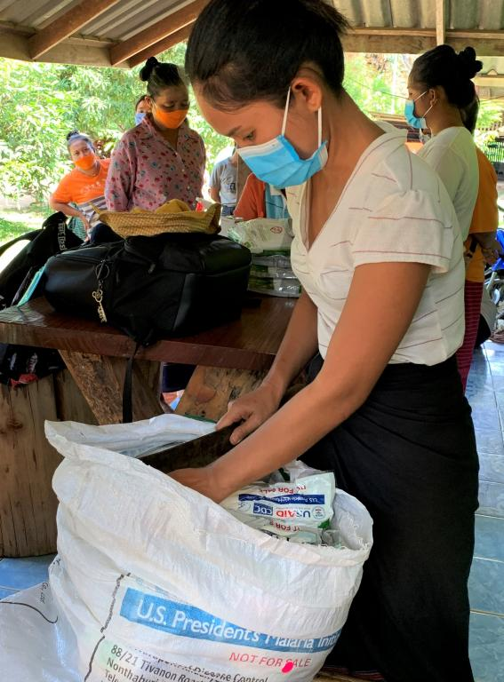 A village health volunteer is preparing insecticide-treated nets donated by PMI to be distributed to the villagers in Sangklaburi district.  A joint field visit with the Division of Vector Borne Diseases (DVBD) and local health office  July 20, 2020  Kanchanaburi, Thailand  Photo by Niparueradee Pinyajeerapat, USAID